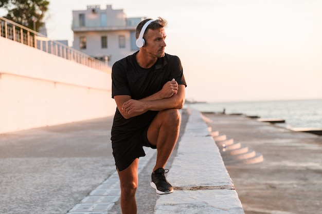 Image of muscular sporty man 30s in shorts and t-shirt walking near seaside, and listening to music via wireless headphones during sunrise