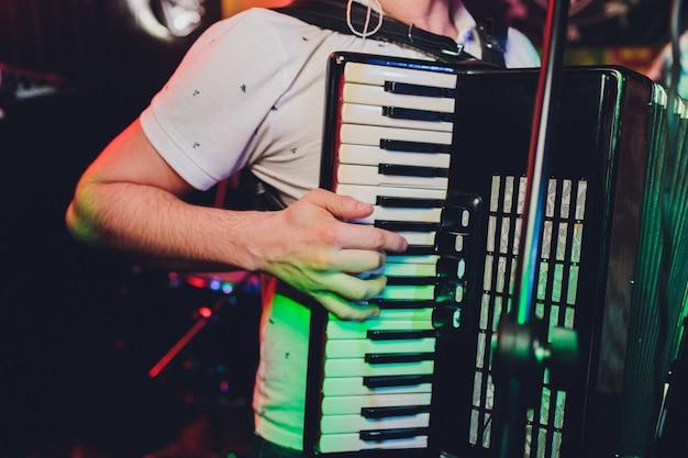Image of musician playing on accordion closeup.