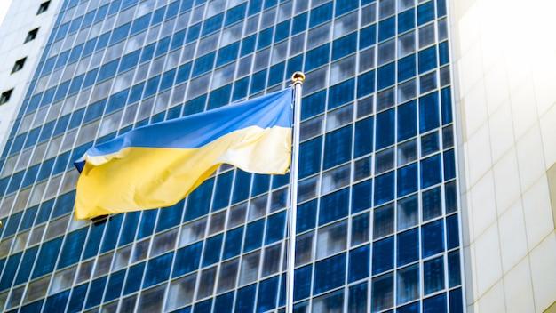 Image of national flag of ukraine against modern office building. concept of ukrainian economics, development and politics
