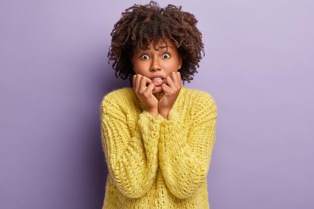 Immagine di una donna nervosa dalla pelle scura morde le unghie per la depressione, si preoccupa per i sentimenti feriti e la separazione con il fidanzato, ha un taglio di capelli afro, indossa un maglione giallo, posa da sola al coperto