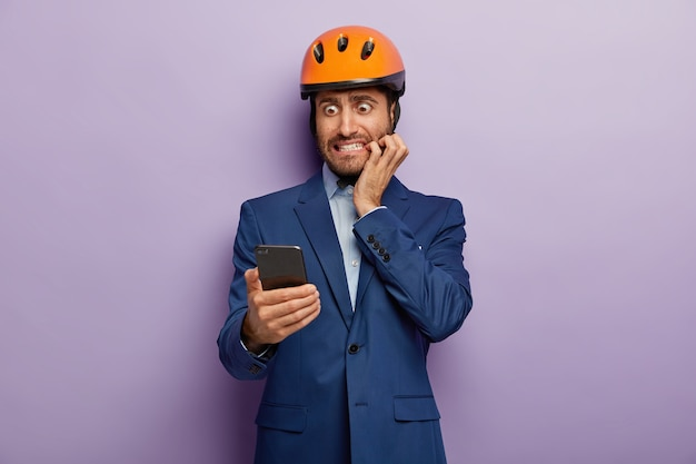 Image of nervous male builder bites finger nails with embarrassement, focused into smartphone device, reads puzzled news happened at work, wears formal suit and hardhat