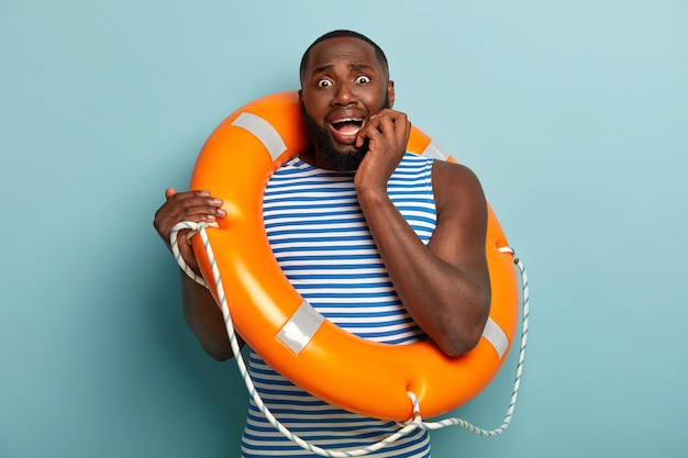 Image of nervous scared man trembles from fear, afraids of swimming without instructor