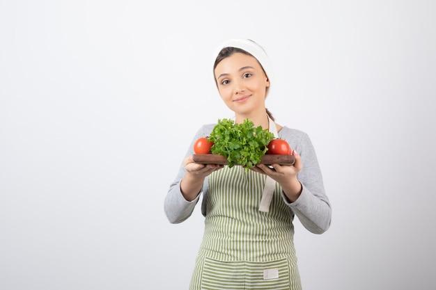 Immagine di una bella donna attraente che tiene una tavola di legno con prezzemolo e pomodori
