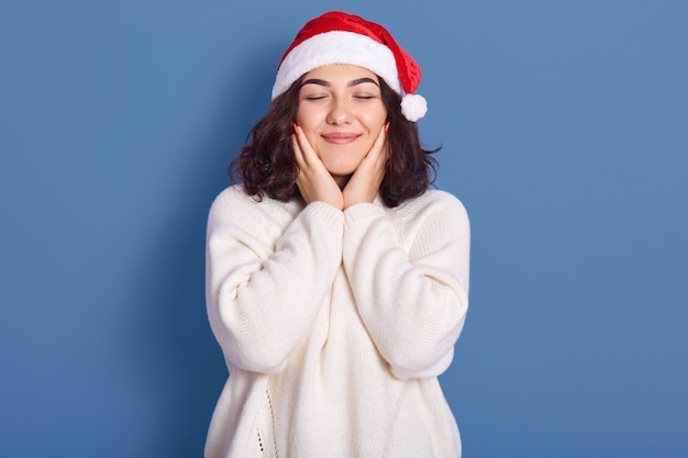 Image of nice young women wearing warm white winter sweater and christmas posing with closed eyes and hands on cheek, posing isolated on blue backgroud, looks chrming and cute. new ear concept.
