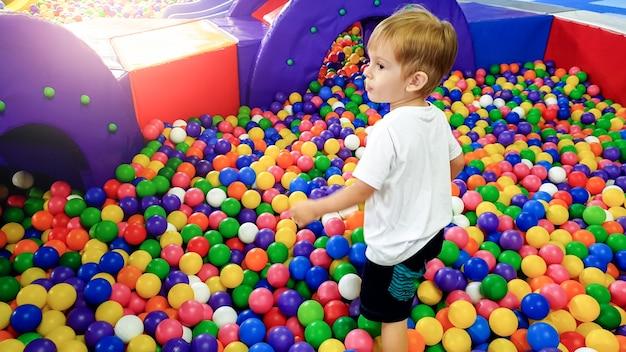 Изображение 3-летнего мальчика, играющего и развлекающегося на детской площадке с большим количеством маленьких красочных пластиковых мячей. ребенок, наслаждающийся парком развлечений в торговом центре
