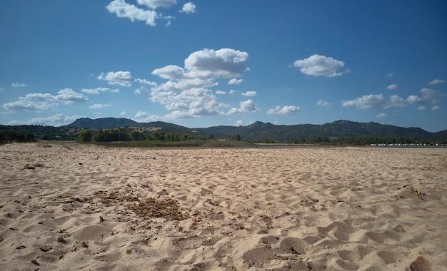 サルデーニャ島のビーチの画像。白昼の羊のような雲と空の下に壮大な山の風景があります。