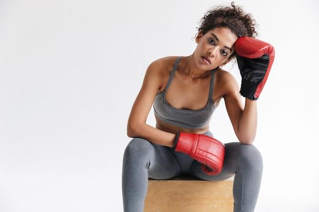 아름 다운 젊은 놀라운 스포츠 피트 니스 아프리카 여자 권투 선수의 이미지는 장갑에 흰 벽 위에 고립 된 포즈.