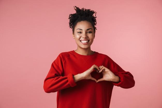ハートのジェスチャーを示すピンクの壁の上にポーズをとって美しい驚くべき若い幸せな興奮したアフリカの女性の画像。