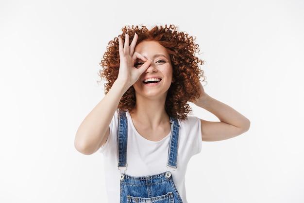 Изображение красивой курчавой счастливой рыжей девушки, позирующей изолированной над белой стеной, показывающей нормальный жест.