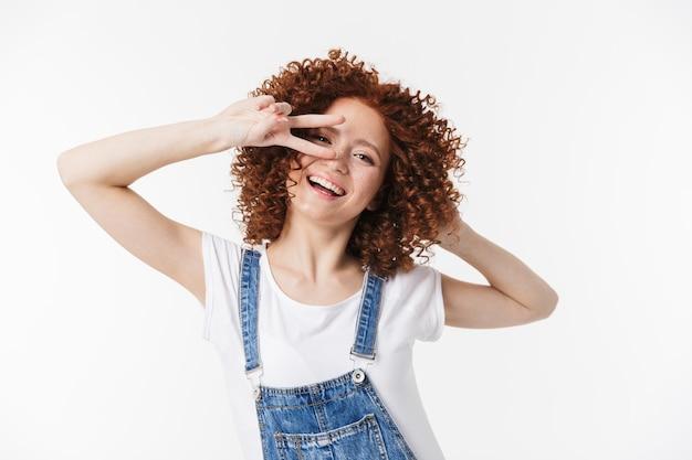 Изображение красивой курчавой счастливой рыжей девушки, позирующей изолированной над белой стеной, показывающей мир.