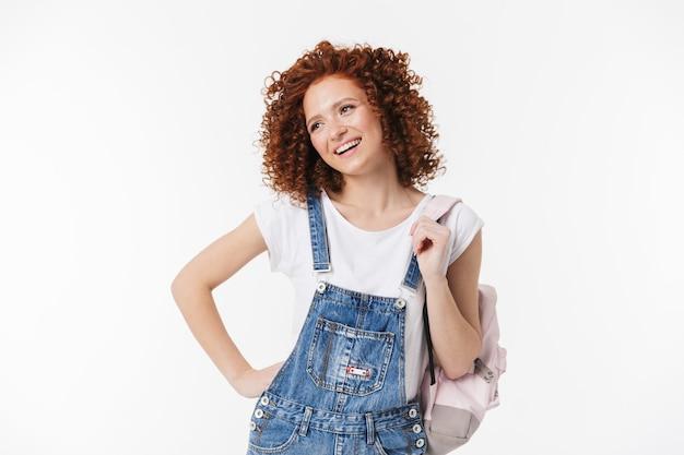 Изображение красивой курчавой счастливой рыжей девушки позирует изолированной над белой стеной с рюкзаком.