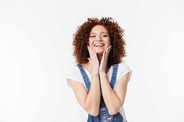 Изображение красивой курчавой счастливой рыжей девушки позирует изолированной над белой стеной.