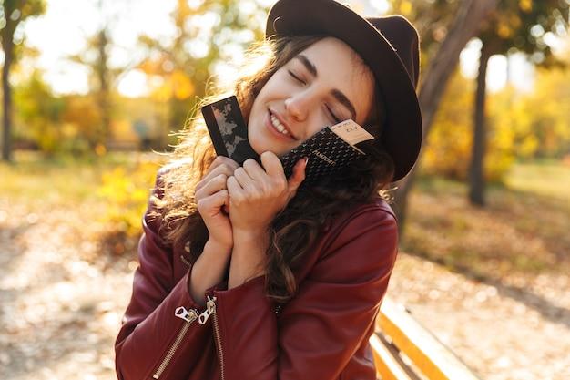 Изображение красивой милой женщины, сидящей на скамейке в парке, держащей кредитную карту и паспорт с билетами.