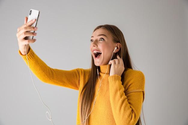 Изображение красивой возбужденной счастливой молодой женщины, изолированной над серой стеной, с помощью разговора по мобильному телефону.