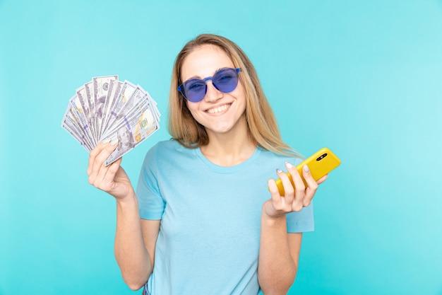 파란색 돈 지폐와 휴대 전화를 들고에 고립 된 선글라스와 함께 아름 다운 행복 한 금발 소녀의 이미지.