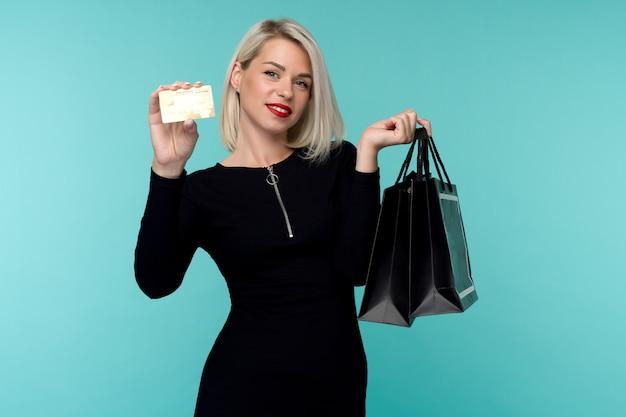 쇼핑 가방을 들고 파란색 벽 배경 위에 절연 포즈 아름 다운 행복 한 젊은 금발의 여자의 이미지