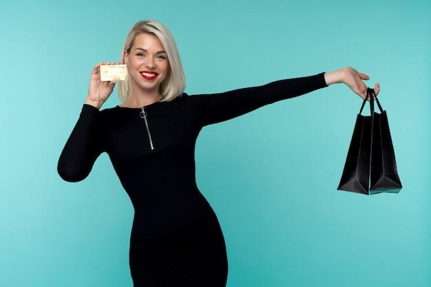 쇼핑백을 들고 파란색 벽에 포즈 아름 다운 행복 한 젊은 금발의 여자의 이미지.