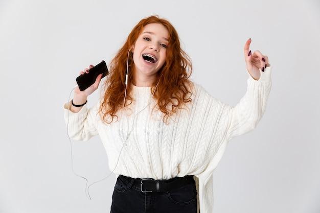 휴대 전화 듣는 음악을 사용 하여 흰 벽 배경 위에 절연 포즈 아름 다운 행복 한 젊은 귀여운 소녀 빨간 머리의 이미지.