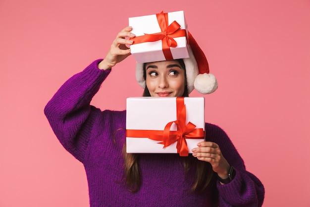 顔を覆うクリスマスの帽子を身に着けているピンクの保持ギフトボックスの上に孤立してポーズをとる美しい幸せな若い感情的な女性の画像。