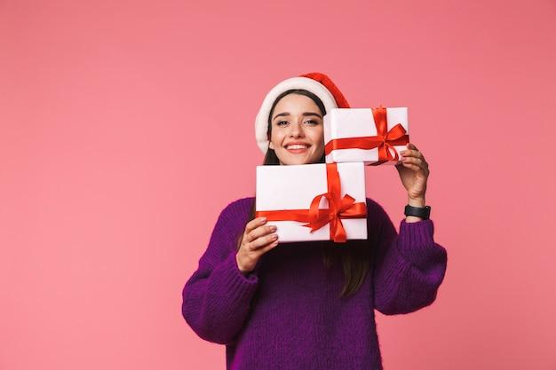 クリスマスの帽子をかぶってギフトボックスを保持しているピンクの上に孤立してポーズをとる美しい幸せな若い感情的な女性の画像。