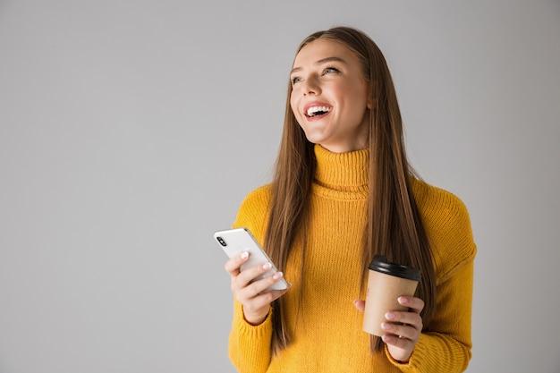 Изображение красивой счастливой молодой женщины, изолированной над серой стеной, с помощью мобильного телефона пить кофе.