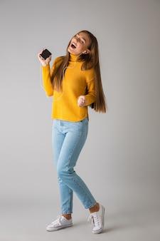 Изображение красивой счастливой молодой женщины изолированной над серой стеной, использующей музыку мобильного телефона слушая с наушниками.
