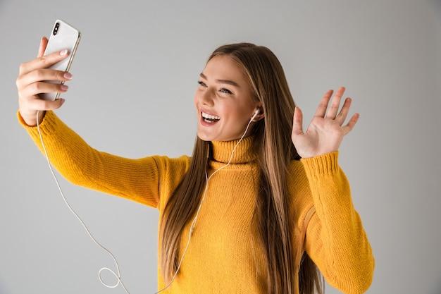 Изображение красивой счастливой молодой женщины, изолированной над серой стеной с помощью мобильного телефона, говорящего размахивая.