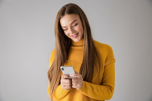 Изображение красивой счастливой молодой женщины изолированной над серой стеной с помощью мобильного телефона.