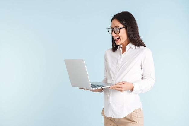Изображение красивой беременной шокировано молодой деловой женщины, изолированной с помощью портативного компьютера.
