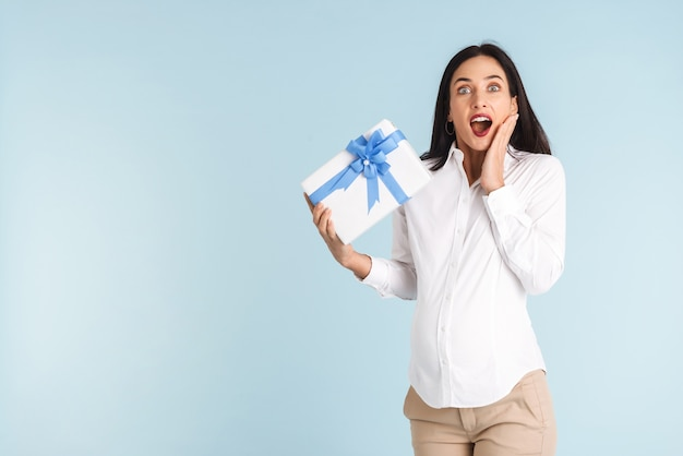 Изображение красивой потрясенной молодой беременной женщины изолировало подарочную коробку холдинга.