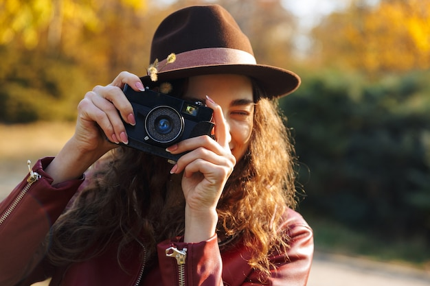 카메라를 들고 공원에서 산책하는 아름 다운 여자 사진 작가의 이미지.