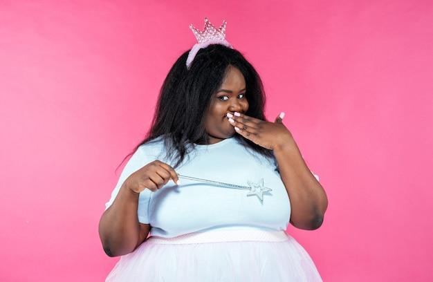 Изображение красивой женщины, позирующей в костюме феи на розовом фоне
