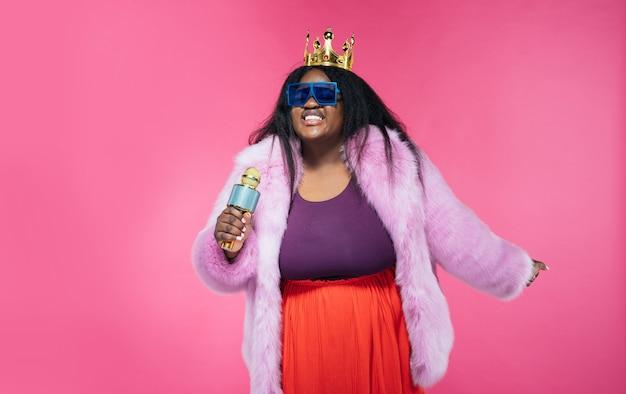 Изображение красивой женщины, позирующей в меховой шубе на розовом фоне