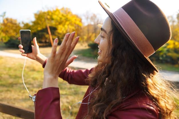 흔들며 친구와 이야기하는 휴대 전화를 사용 하여 공원에서 산책 앉아 아름 다운 여자의 이미지.