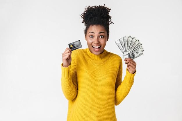 Изображение красивой молодой африканской возбужденной эмоциональной счастливой женщины, позирующей над белой стеной, держащей деньги и кредитную карту.