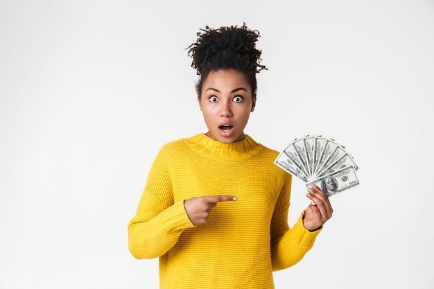Изображение красивой молодой африканской возбужденной эмоциональной счастливой женщины, позирующей над белой стеной, держащей указывая деньги.