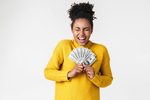 Изображение красивой молодой африканской возбужденной эмоциональной счастливой женщины, позирующей над белой стеной, держащей деньги.