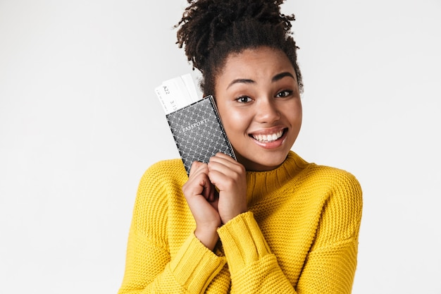 Изображение красивой молодой африканской возбужденной эмоциональной счастливой женщины, позирующей над белой стеной, держащей паспорт с билетами.