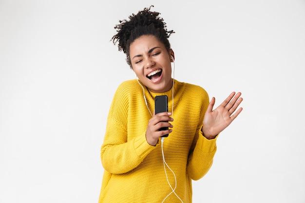 携帯電話の歌を使用してイヤホンで音楽を聴いて白い壁の上でポーズをとる美しい若いアフリカの興奮した感情的な幸せな女性の画像。