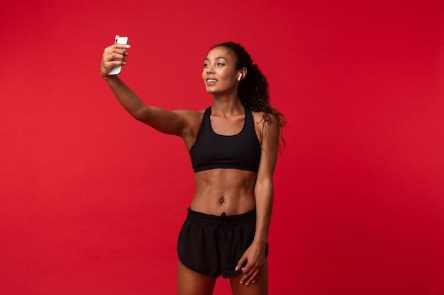 Изображение красивой молодой африканской спортивной фитнес-женщины позирует изолированной над красной стеной, слушая музыку с наушниками, делает селфи по мобильному телефону.