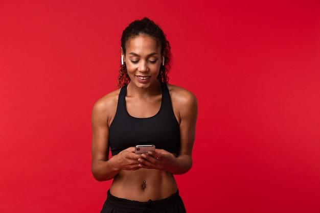 Изображение красивой молодой африканской спортивной женщины фитнеса, позирующей изолированной над красной стеной, слушающей музыку с наушниками, с помощью мобильного телефона в чате.