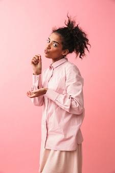 Изображение красивой молодой африканской женщины, позирующей изолированно, представляет, что она пьет чай. Premium Фотографии