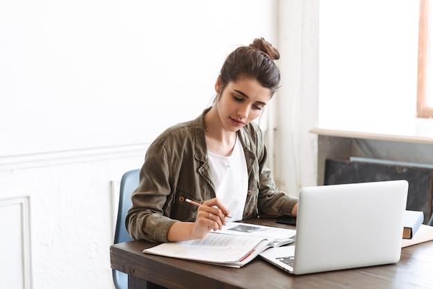 Изображение красивой молодой сконцентрированной женщины, использующей портативный компьютер в помещении, написание заметок в записной книжке.
