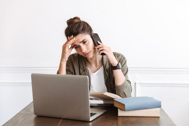 Изображение красивой молодой запутанной недовольной женщины, использующей портативный компьютер в помещении, разговаривает по мобильному телефону.
