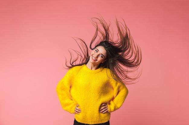 ピンクの揺れる髪の上に孤立してポーズをとる美しい若い感情的な女性の画像。