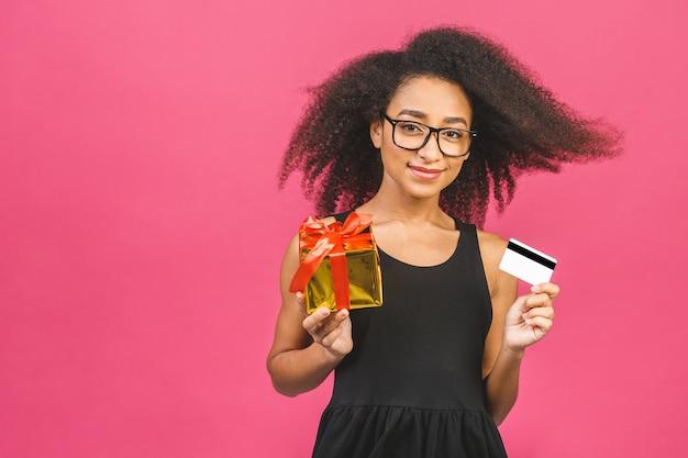 Изображение красивой молодой возбужденной эмоциональной счастливой женщины, позирующей над розовой стеной, держащей кредитную карту и подарочную коробку.