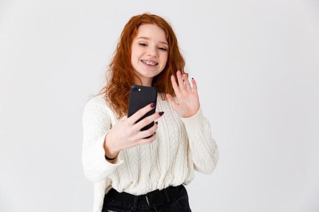 Изображение красивой молодой девушки, рыжая позирует, изолированные на белом фоне стены, делает селфи.