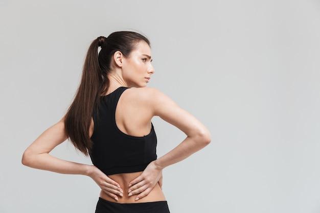 회색 벽에 고립된 요통을 가진 아름다운 젊고 슬픈 스포츠 피트니스 여성의 이미지.
