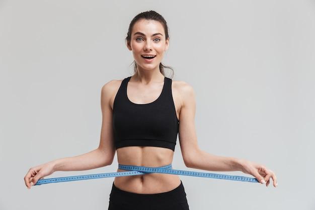 아름 다운 젊은 스포츠 피트 니스 흥분된 행복 한 여자의 이미지는 회색 벽에 고립 된 허리에 센티미터와 함께 포즈.