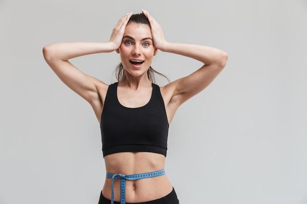 美しい若いスポーツフィットネス興奮した幸せな女性の画像は、灰色の壁に隔離された腰の上のセンチメートルでポーズをとっています。